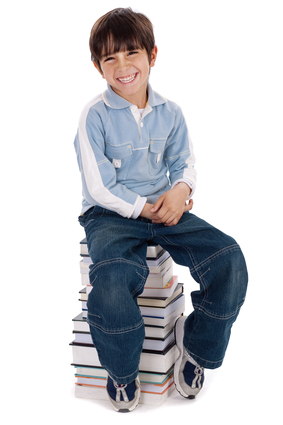 Smiling young kid sitting over pile of books